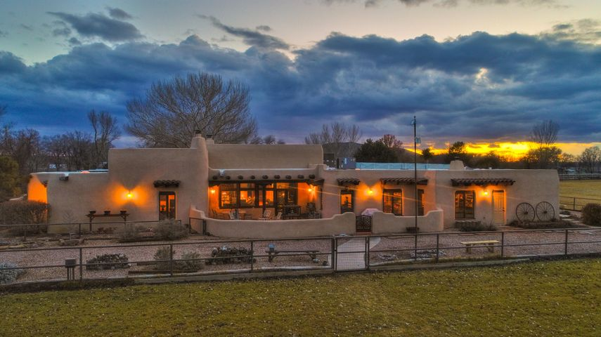 Renowned adobe home designer/builder Nick Garcia created this architectural treasure to dazzle with 16' beamed-ceiling great room & soaring wood-burning fireplace, brick/saltillo/wood floors, hand-crafted custom windows, 2 master suites with kiva fireplaces & adjoining walled patios, round dining room overlooking gardens & pool, 4 walled courtyard/patios with brick decks & beams, granite counters, active solar, 300 amp electric service all on 8.67 acres  w/ 7-horse barn, tack room, huge hay barn w/bath, loafing sheds, lighted arena, round pen, arena mix riding soil, lush laser-leveled grass hay field, pipe/coyote fencing, 3 wells, views of Tome Hill.  2 laundry rooms & workout room.  Immaculate landscaping on sprinkler system.  Radiant & forced air heat. Refrigerated air. Sell all or part