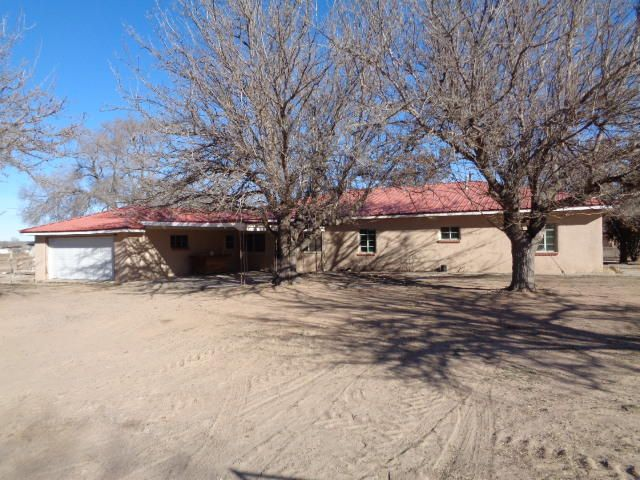 Recently remodeled adobe home on 3.71 acres!!  Includes new interior paint, flooring, appliances, garage door and stucco/paint.  It has a large living room plus big den with brick fireplace.  There is a formal dining room plus breakfast nook off the kitchen which has a walk-in pantry.  There is a mud sink and broom closet in the laundry room.  The main house has 2 bedrooms with walk-in closets plus an office (potential bedroom) and 2 bathrooms.  The guest quarters has 1 bedroom with built-in drawers and bathroom.  It has a 500 SF enclosed patio, two-car garage and carport.  The covered entryway has brick planters.  All under one metal roof.  It has a block storage barn that was used for milking plus 20x64 block structure with 4 bays and storage room.  Horses okay. Additional acres avail.