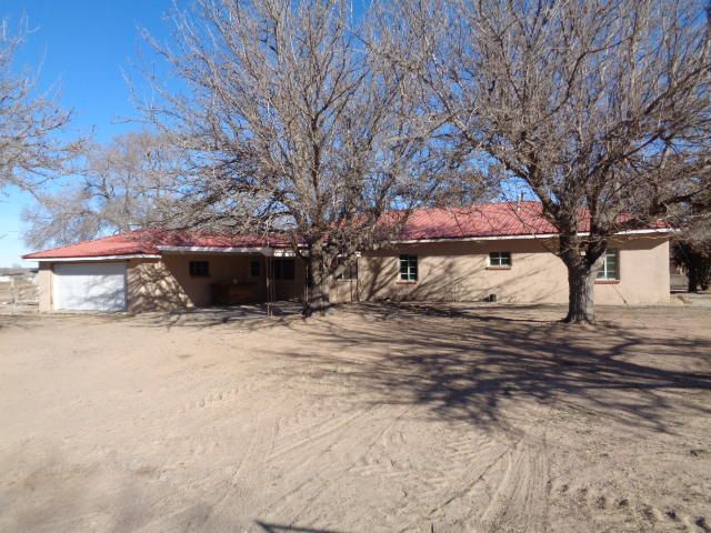 Recently remodeled adobe home on 5.29 acres!!  Includes new interior paint, flooring, appliances, garage door and stucco/paint.  It has a large living room plus big den with brick fireplace.  There is a formal dining room plus breakfast nook off the kitchen which has a walk-in pantry.  There is a mud sink and broom closet in the laundry room.  The main house has 2 bedrooms with walk-in closets plus an office (potential bedroom) and 2 bathrooms.  The guest quarters has 1 bedroom with built-in drawers and bathroom.  It has a 500 SF enclosed patio, two-car garage and carport.  The covered entryway has brick planters.  All under one metal roof.  It has a block storage barn that was used for milking plus 20x64 block structure with 4 bays and storage room.  Horses okay.