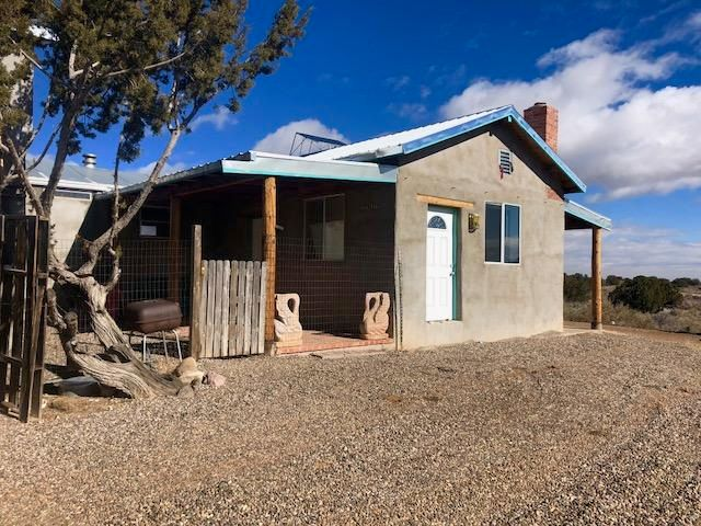 OFF THE GRID LIVING!  Peaceful and Private Location With Panoramic Views of the Sandia Mountains on 1 AC.  Single wide 2 bedroom/1 Bath with an additional  320 Sf Adobe Greatroom! Wood Burning Kiva Fireplace,Brick Floors, Beautiful Beamed Ceilings.  Propane Refrigerator, Range & Stove All Convey! Self Reliant No Utilities to Pay!