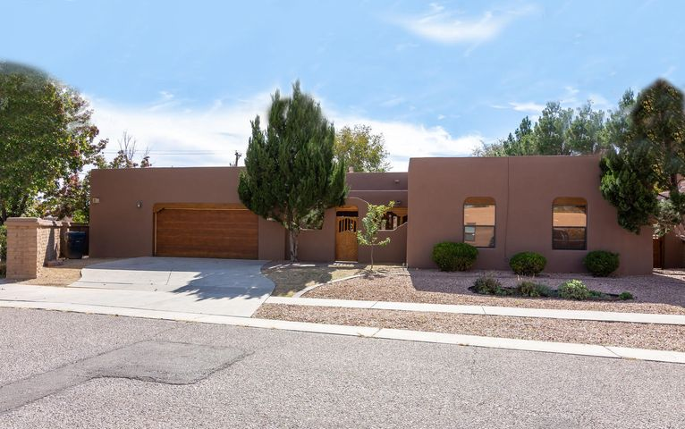 Captivating single level custom boasting a touch of Santa Fe with southwest charm, nestled on a corner, cul-de-sac lot in the beautiful North Valley; close-in & convenient to Old Town, downtown, Rio Grande Nature Center & easy I-40 access. Lovely courtyard entry! Meticulously maintained, showcasing fine attention to detail! Spacious, bright & open floor plan w/ generous size rooms, brick floors gracing the entry, living, dining room & kitchen; raised ceiling with 10 foot T&G beam ceilings, 2 kiva fireplaces, exposed adobe, smooth plaster walls, skylights, NEW carpet! Kitchen offers abundance of cabinetry, breakfast bar; Large master with jetted tub, 2 walk -in closets! Private & large backyard w/ 18x11 covered patio! Refrig. Air! New stucco! Oversized 2 car garage with workshop area!