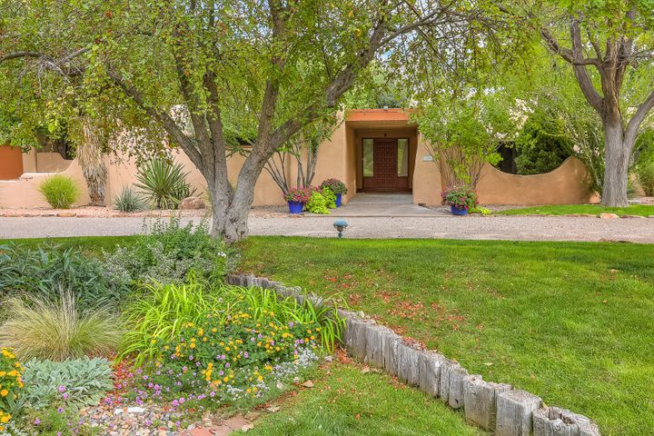 Rare find in this special pueblo revival home in the coveted El Caballero Ranchitos neighborhood in the verdant North Valley. Lush landscaping and a tree-lined acreage lead into a gracious courtyard and gallery entry.Options for living and entertaining include  a formal living room with fireplace, dining room and a splendid large family room with fireplace, bookcases and a private patio. Gather around the center island in the updated kitchen which features granite and SS appliances. The master suite has a closet to die for! Adjacent to the master is a very large office/studio with a separate entrance. There is lots of space in the four additional bedrooms. A gathering area for meals or relaxation and conversation is the light center atrium. Sweet guest house with BR, BTH, FP & garage