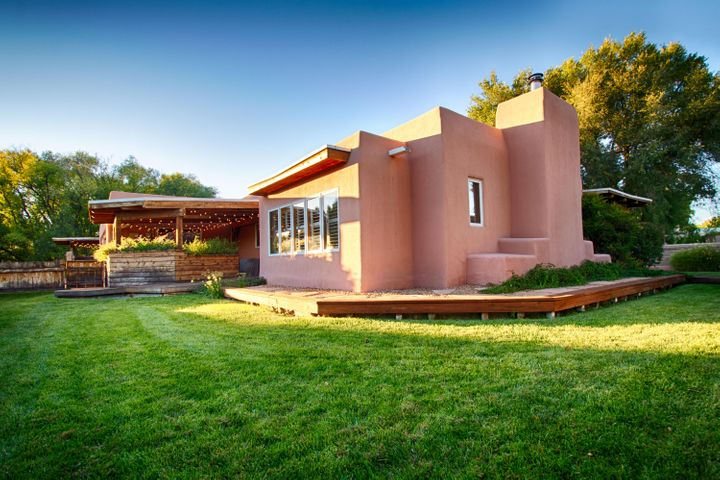 A PIECE OF PARADISE- Beautiful and spacious, inside and out.  This adobe home, designed and built by Terry Taggert, has an authentic character and charm that is completely true to its architecture.  You will be drawn in by the many amenities and high-end features of this North Valley beauty.  Designed for entertaining: three covered patios, & a gourmet kitchen with top-of -the-line Wolf & Jenn-Air appliances (two wine ridges, full-size freezer, two-drawer dishwasher, built-in Miele coffee maker), & stunning travertine countertops that offer generous food preparation space.  Two master suites, and a split floor plan provide for multi-generational living.  This spacious home also features a separate guest house- great for in-laws, out-of-state guests, or your college student.