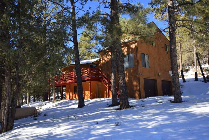 Five acres of towering Ponderosa pines surround this unique mountain retreat. Main living area of the house is at  treetop level offering a beautiful setting. This home has a remodeled kitchen, new furnace, wood burning stove, along with 2 living areas, 3 bedrooms and two and half baths. The master bedroom offers a loft area great for an office or study, as well as a huge walk in closet and bath room with a claw foot tub. Down stairs you will find a 2 car garage, a game room , laundry area and half bath. This one of kind home is wrapped with a deck for enjoying the summer breezes. This property makes for a peaceful retreat all year round.