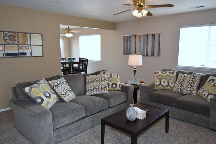 Wonderful ground floor unit!  A light and bright floorplan welcomes you to this well kept home.  Living room has cozy gas fireplace, built in nichos, and ceiling fan. Two spacious bedrooms with good sized closets.  Back patio is fenced for privacy and perfect for BBQ's!  No neighbors behind, backs to open space.   Refrigerated AC.  Stunning Sandia Mountain Views.  Close to shopping and restaurants.  Newer carpet and paint. One car garage!