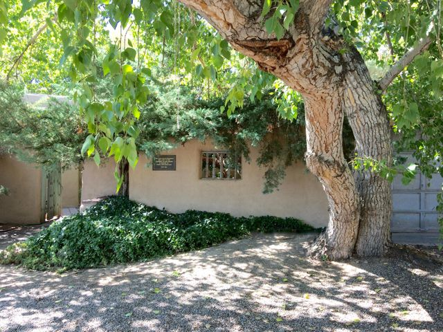 Iconic North Valley Nat Kaplan compound on the Bosque!  A serene setting that includes a main house, guest house and art studio/guest house. All adobe construction with brick and exposed concrete floors, white washed walls and kiva fireplaces throughout. A  courtyard connects the main house to guest house. A light filled circular art studio looks out to the natural beauty of the Bosque. The studio can double as a guest house with a full bath and separate bedroom. All of this on .6 acres with access to the Bosque and water rights for irrigation.  Radiant heating in the main & guest house.  Newer TPO roofs, 2 new boilers and newer stucco.
