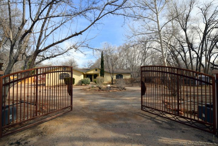 WHAT AN OPPORTUNITY, at a GREAT PRICE to have A Rio Grande DREAM Hacienda, Single Story Home! Beautiful gated entrance leads you to 2.8 aces w fruit trees and irrigation - the Green Belt! Floor plan offers lots of options to fit any of your needs! 3 car attached garage + storage & Workshop/Barn. Formal areas & relaxing separate rooms! Kiva fireplaces, Soaring Beamed ceilings, adobe walls & Light filled windows! 4 beds + office or 5 beds, Separated Master Suite w spacious bath & dual walk-in closets + 2nd master w bath. Cook's Kitchen w island, breakfast nook & large pantry! This one is VERY Special! Do not miss out on this outstanding property!