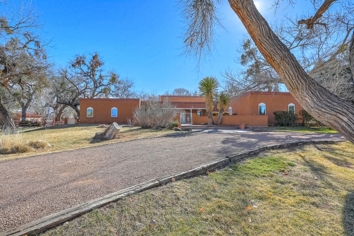 Don't miss out on this picturesque 2.25 acre estate in Corrales Del Norte with sprawling lawns and big trees. Equestrian enthusiasts will cherish the 4 stall barn, tack rooms, hay storage, office, turn out pens and room for an arena. Close to the Bosque, the trails are numerous. The recently refreshed home features a large living room with a high wood ceiling and kiva style fireplace, a second living area is cozy and warm with a 2nd kiva fireplace. The bright and spacious kitchen offers plenty of counter tops, cabinets, a gas range and island. The master suite is ideally separated from the opposite side of the home that features 3 additional bedrooms and two bathrooms. Multi-generational  living is easy with an in-law suite or second master. Enjoy the private back porch & secluded pool.