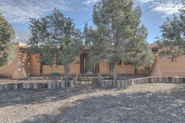 Beautiful North Valley Adobe home on a half acre lot.  Tons of South West charm and character in this former antique store that features stained glass windows, custom made doors and wood work, old world vigas, claw foot bath tub, brick floors and antique light fixtures.  This unique adobe home is a hidden gem.  You will be amazed by the architectural details and one-of-a-kind style this  fabulous home has to offer.  The huge front and back yards have fun and creative landscape, flagstone paths, incredible views of the Sandia Mountains and an amazing latilla covered patio just off the huge sunroom.  Plenty of room and conveniently located to schools, shopping, restaurants, Rail Runner and more.  Make an appointment to see this incredible home today.