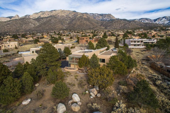 Absolutely fabulous custom Sandia Heights home with expansive mountain & sunset  views!  The open floor plan is full of sunshine and lends itself to the perfect entertaining home and family home with plenty of space for everyone.  The chef's kitchen with granite counters and stainless steel appliances is the hub of the open living and dining areas that are surrounded with views from the east and west balconies. 1 level of the home provides 3 bedrooms with a spacious game room/family room complete with a sink, small refrigerator and dishwasher.  Fabulous amenities throughout...Entire home just restuccoed, 2014 refrigerated A/C, Quality Hurd Metal Clad Thermal Windows, spacious &  enclosed grass area, large enclosed RV parking, 2 fireplaces, jetted tub.  Inspections & repairs complete!