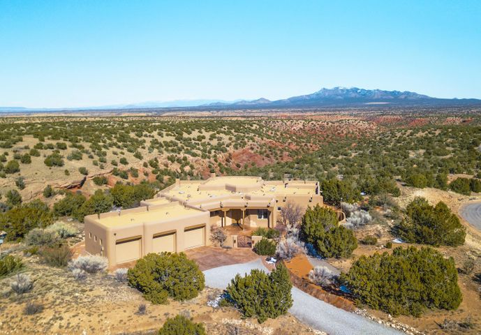 Exquisitely designed custom built home situated on 10 acres in the Premier San Pedro Creek Estates subdivision. Carefully designed to take advantage of 100-mile unobstructed views of the Red Rock Canyons, Sangre de Cristo & Ortiz mountain ranges, along with the twinkling lights of Sante Fe at dusk. Upon entry, the inviting foyer conveniently branches off to any part of the home. The main living room showcases a large wall of custom wood casement windows ascending up to a gorgeous herringbone viga-beamed ceiling. Nestle around the cozy kiva gas fire while enjoying movies or your favorite tunes from the built in entertainment system. The open kitchen layout allows for perfect entertaining, featuring SS appliances, large kitchen island, beautiful granite counters, wine chiller, pantry, custom