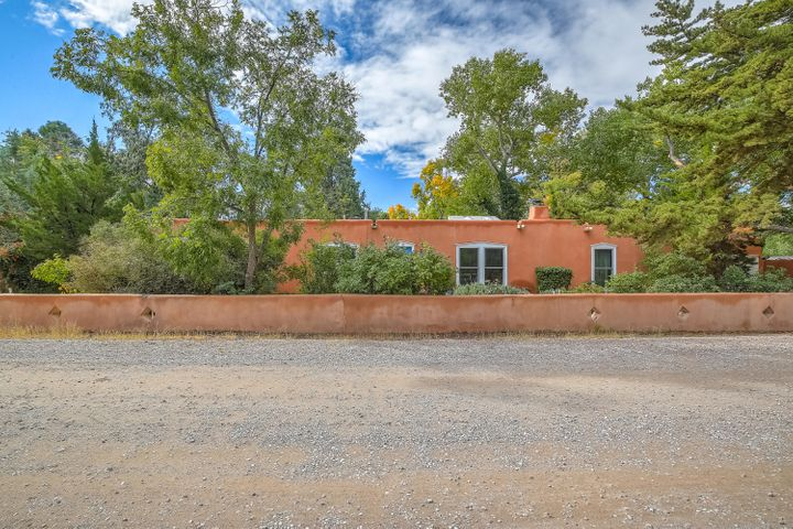 This quintessential Santa Fe style adobe home is a rare find! It sits on one of the North Valley's most charming streets & has been lovingly remodeled with gorgeous materials and design concepts. The grounds look like a private park & the property is a gardener's delight with mature trees, fruit trees, lavender, perennial flowers, shrubs and grass and a lovely pool & cabana area.  The home features brick floors and beamed ceilings throughout.  There are three, cozy fireplaces, two are authentic wood-burning kivas & the third is gas log. The kitchen and baths have been remodeled with stunning, hand painted tile, granite or marble counter- tops & custom cabinetry. The solarium has new sliding doors and brings the outdoors in, year round & is fabulous for entertaining! This home is special!