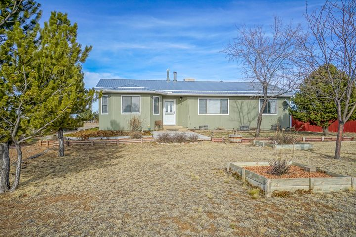 A beautiful country retreat less 45 min east of Albuquerque! This gorgeous remodeled 4 bedroom, 2 bath, single story 2,372 sqft ranch style home on an over 1 acre corner lot offers a brand new kitchen, updated bathrooms and beautiful outdoor living space. This cared for home boasts an open concept living area with a finished walkout basement for extra flex space. The exterior has new siding and paint, seamless gutters and newer propanel roof. The front yard is fully landscaped offers gorgeous curb appeal. Mature pine trees create cooling shade and privacy along with plenty of room for all your toys. The fully fenced backyard oasis features a beautiful new deck, hot tub, new septic, xeriscape and grass. MOVE IN READY!! Carpet allowance with acceptable offer.