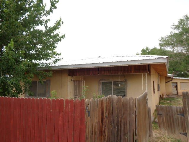 Older adobe home located on .70 acre. It has 5 bedrooms and a full bath. Single-wide mobile home also located on property. Per zoning, two living quarters are allowed now, but cannot be replaced as only one residence per lot is permitted in R-1A. Detached storage. Structures need work.