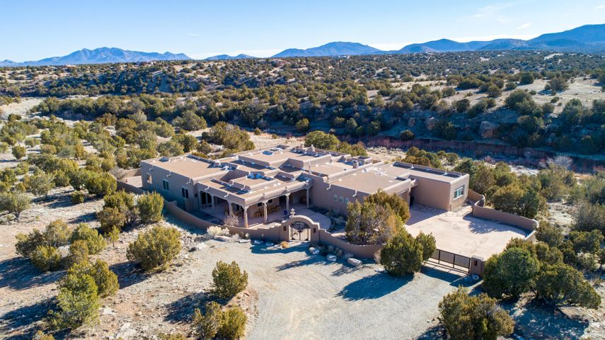 Open Sat 3/16, 1-3pm, Sun 3/17, 1-4pm.  Enjoy the babbling SAN PEDRO CREEK flowing in the backyard of this stunning Home in a Fabulous CANYON SETTING.  Backing up to the Nature Preserve and Open Space with the San Pedro Mountain Range as its backdrop, this gorgeous home beckons you from the Turquoise Trail. Wonderful open floor plan, perfect for entertaining, with huge living room featuring a stunning custom fireplace which opens to the impressive outdoor patio. Fully appointed kitchen with fireplace, formal dining, built-in bar and cabinetry, large exercise/game room with wood floating dance floor, interior IN-LAW SUITE, spacious office, exquisite master suite, beautiful front patio & courtyard, and gated driveway. 2 minutes to the Paa-ko Ridge Golf Course and only 40 Minutes to Santa Fe