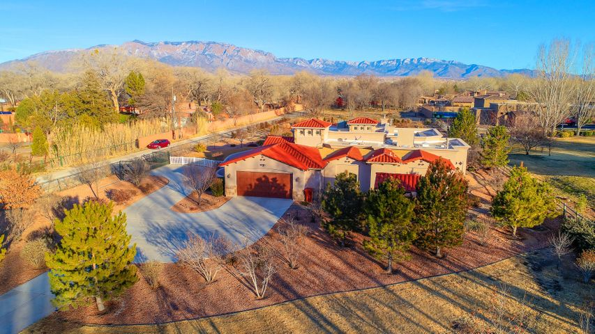 CORRALES BEAUTY!! Gorgeous Custom Home Built in 2012 sits on 2.15 AC with wonderful views of the Sandias!  Every corner of this home and lot were carefully and meticulously thought out!  Home has two master suites! The main master is 20.6 X 20.8 w/ His/Hers Closets, Gas FP. Office/3rd BR with built in bookcases.  215 SF Sunroom off the master is heated/cooled but not included in SF. 12' Ceilings in LR and Kitchen, 18' ceiling at Foyer, 10' Ceil at Master, hardwood flooring throughout, Cherry Wood Cabinetry, beautiful granite, butlers pantry, Wolf Sub Zero Fridge, 2 Wolf Ovens, Miele DW,  Pella Windows and Doors, Owned Solar Panels, Radiant Heat 5 zones and Central Heat system, REF Air, Calif Closets. 1200 SF Barn/Workshop can house an RV, also has a small living area and 3/4 bath! See More
