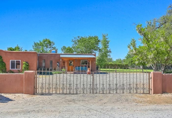 Charming 100-year-old Thick-Walled Adobe, High Ceiling Liv Rm w/ Vigas & Wood Ceiling, Corner Kiva w/ Plaster Banco, frame Kitchen & Half-Bath not quite so old, private & peaceful, surrounded by a stucco wall, Detached Carport/Storage, Grass Yards, Mtn Views, Patios, Trees & Flowers, Greenbelt Location near Acequia for walks, Metal Gate off Perea Rd, Walk to shops & restaurants, 54 feet of frontage on Corrales Road, Zoning allows for dwelling & a commercial structure, thus business OK too. Because in Neighborhood Commerical Zone, Village of Corrales requires buyer to connect grey water to sewer system, small fee for residential connection, seller willing to assist