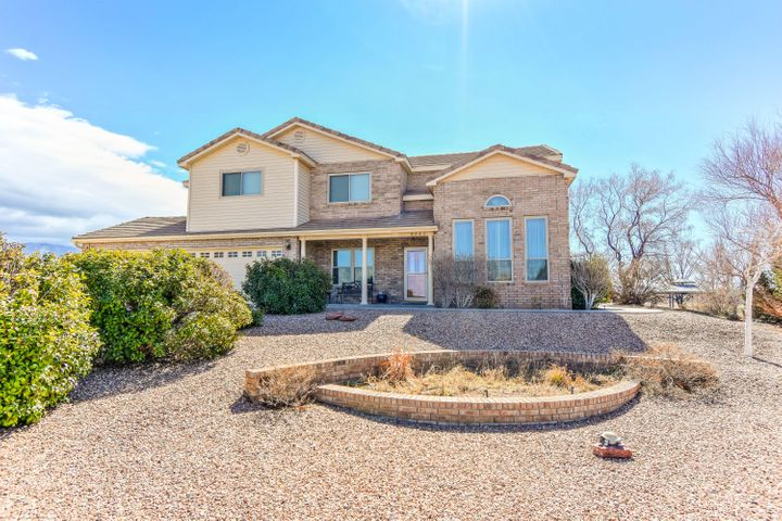 Gorgeous custom built North Albuquerque Acres home on a generous .89 acre property with impeccable mountain views! Great floorplan featuring 3,194 sf with 5 bedrooms, 2.5 bathrooms, 2 living areas and a 3- car garage! Kitchen fit for a chef with brand new granite countertops, ample cabinet space, upgraded stainless range, dishwasher, microwave, refrigerator, center prep island, breakfast nook, wet bar and a built-in work area. Open living area with a beautiful gas fireplace & built-in bookshelves!  Hardwood staircase leads you upstairs to the spacious master suite with a private enclosed balcony and spa-like bath! Bath w/ dial sinks, jetted tub, walk-in shower and closet!Amazing backyard w/ 2 covered patios, and custom pergola to  take in those watermelon sunsets. Storage shed included!