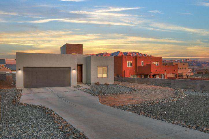 This stylish, sophisticated and state-of-the-art GREEN contemporary residence is nestled in the heart of Rio Rancho on a large 1/2 acre lot with impeccable views. The generously proportioned interior flows effortlessly from the open-plan living space to the private covered patio complete with an outdoor kitchen. With cathedral ceilings and stunning floor to ceiling custom tile fireplace as well as plush lighting, crisp grey walls along with luxuriously painted specialty variance finished accent walls and contrasting white baseboards, the styling in this home is unmatched. The well-appointed modern kitchen includes custom cabinetry, granite counter tops, farmhouse sink, quality appliances and a large pantry along with ample seating at the bar-top leading to a spacious living room and...