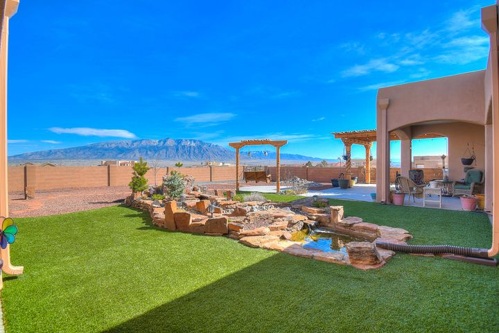 Open House 3/24 1-3pm!! Breathtaking Panoramic Sangre' de Cristo, Jemez & Sandia Mountain Views from this Expansive custom massively renovated executive retreat. Romantic Owner's Suite, Coving & Crown Molding, whirlpool view tub, double sinks in creamy marble vanity, his & hers water closets & bidet, snail shower, trendy barn door hides large walk in closet. Dacor 6 Burner Cooktop in Gourmet Kitchen, true double ovens, 'furniture like' soft close cabinets, quiet Bosch dishwasher; Hickory Hardwood floors;  exquisite staircase to stunning Viewing Deck; Radiant Heated floors plus backup forced air HVAC system. Lots of storage. Backyard Paradise! So much covered space with wrap around portale, hand built solid beautiful ramada perfect to add a hot tub, peaceful waterfall river feature;