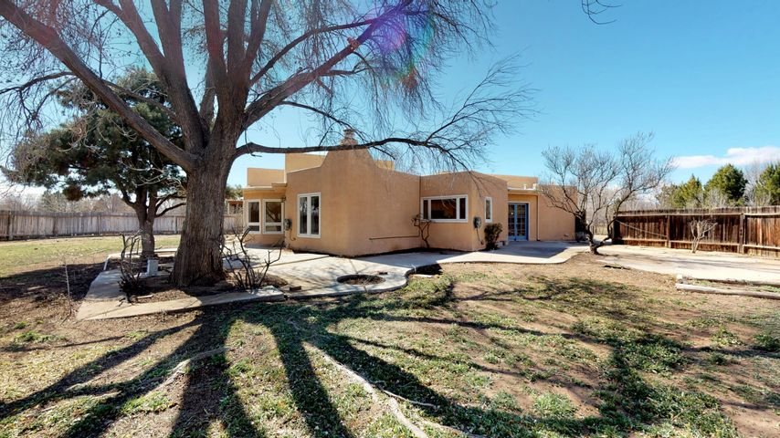 Spectacular North Valley property in the El Caballero Norte neighborhood with 1.28 acres on a cul de sac lot. This Home Offers Approximately 2700 square feet with 3, possible 4 Bedrooms and 2 full bathrooms. The home has a beautiful chef's kitchen with large island and eat in area, refinished wood floors, gorgeous living room with kiva fireplace and bay window, wood beam accents, nice neutral colors throughout.  Detached 2 car garage and another detached building that can be used for additional vehicles.  City water and sewer water too!   A Great Value For One Of The Most Desirable Neighborhoods In Los Ranchos!  Come take a look!