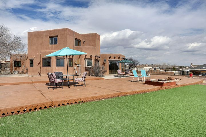 VIEWS, MEGA PATIO, BIG SKIES, CHARACTER, REFRIG AIR.. BINGO! Explore this unique home perched high on a .47ac lot. Enormous patio with custom decking including a built in fire pit & water feature. Enter into brick floors & a wall of windows framing the Sandias. Eye candy! The home is bright & open, kitchen is well laid out w stone counters, gas stove. Lg util room is adjacent to kitchen with extra pantry/storage. Master on main floor has adjoining office/rec space. Custom made bathroom suite, LG walk in closet, 2 sinks, fun bathtub, sep shower. Up a few stairs beds 2&3 w amazing views out all triple pane windows. 3rd bdrm has walk in closet & walkout patio for star gazing. Backyard has raised garden beds, plenty of space for anything. 2 car gar & carport. If must have views this is IT!