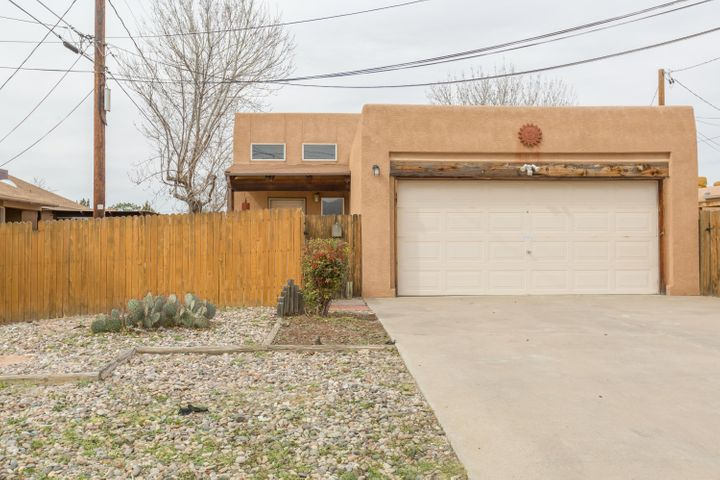 Come see this bright and airy, open floor plan home.  Vaulted ceilings, wood vigas, kiva fireplace, clerestory windows and sliding glass doors, skylights, ceiling fans, new floors in all living spaces, new water heater, large yard, large garage. Close to UNM and easy to show!!