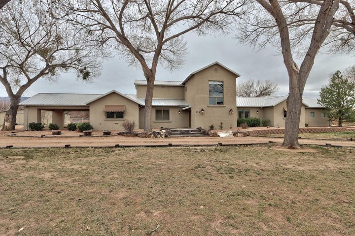 Spectacular Northern New Mexico style custom home situated on rare 2+ acres on the east side of Corrales Rd. w/ direct access to endless miles of riding & walking trails along the bosque & Rio Grande. Flooded w/ natural light the main house features 2 living areas, custom wood windows & doors, refrigerated air & both radiant & central forced air.  Open floor plan w/ 20'' Italian tile floors leads to exceptional outdoor living space featuring kiva fireplace, flagstone patio & spectacular mountain views. Two bedrooms w/ shared bath on first floor could be master suite. A horse owner's dream estate boasts a 3-stall Barn Master steel barn w/ water & electricity, piped fencing, & shade in summer for your horses. Bring your animals & green thumb to this private & gated Corrales oasis!