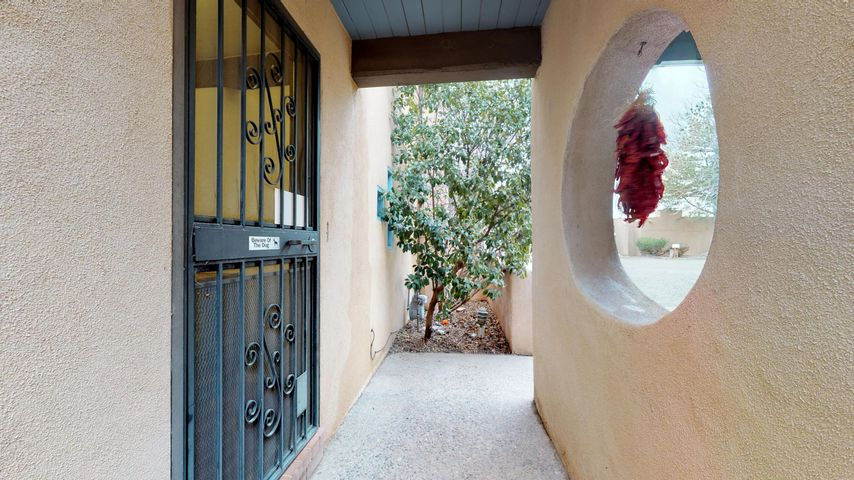 Beautiful southwestern adobe townhouse nestled in the North Valley & conveniently located in the exclusive Guadalupe Del Prado Community. Close to the Bosque & Los Pablanos fields for bird watching, biking, trails & more. Great floor plan w/exposed beams, red brick floors, built-in book cases & Kiva fireplace. Spacious kitchen w/granite counters, updated appliances, newer sliding glass doors & breakfast nook. Covered patio is great for BBQ's & entertaining. Recently upgraded Heat/Cool combo unit. Two car covered carport w/oversized workshop/storage area. Upstairs enjoy the large master bedroom w/huge walk-in closet, big remodeled bathroom w/soaking tub, & adjoining private office/study w/mini-split system. Don't forget about the exclusive community pool-all the benefits-none of the upkeep!