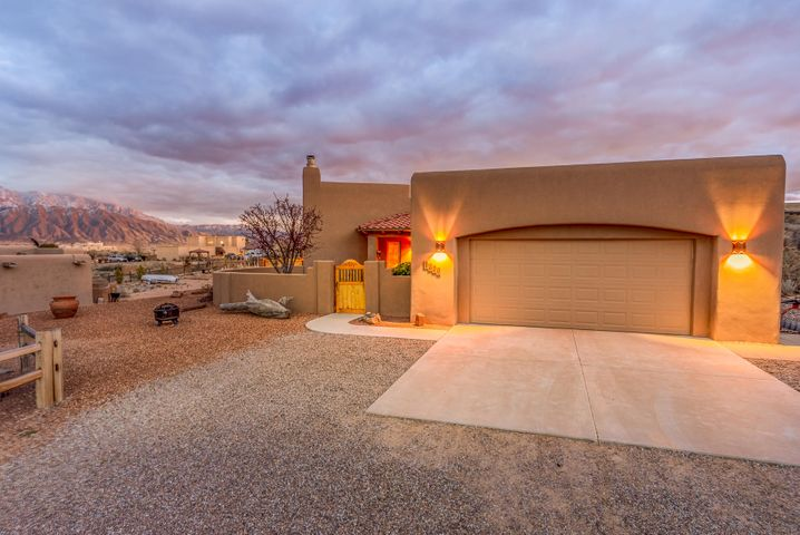 Exceptional VIEWS of the Sandia Mountains from this Gorgeous CUSTOM built home on half an acre in Rio Rancho Estates. Enter through the front courtyard into the spacious great room featuring a tongue and groove raised ceiling with Vigas, corbels, a  gas lighting kiva fireplace, and a wall of windows showcasing the sweeping mountain views. Skylights and nichos are additional features in this home. Fully landscaped front and back. Tile flooring throughout living area, kitchen and baths. Spacious master bedroom that also has mountain views.  Come fall in love with this beautiful home!