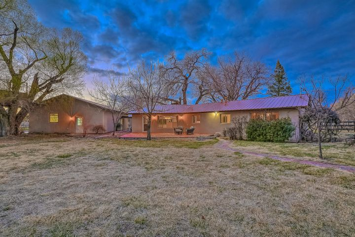 Amazing opportunity to own close to 2 acres backing up to the Rio Grande River in the middle of Albuquerque!  Listen to the sandhill cranes flying over as you pick apples, plums, cherries and more in your orchard.  Watch the sunset pink up the Sandias as you sip your favorite drink in solitude.  The home is a tastefully remodelled ranch with newer synthetic stucco, metal roof, and HVAC system.  The entire home has been redone with granite counters, new cabinetry, new wood-look tile floors, appliances, & hardware.  Plus you get a large 4 car garage and a horse-ready barn with a tackroom.  But the crowing jewel is the rare, private location on 2 acres, on a quiet street in the heart of the city.  For the discerning buyer who understands it is all about location, location, location!
