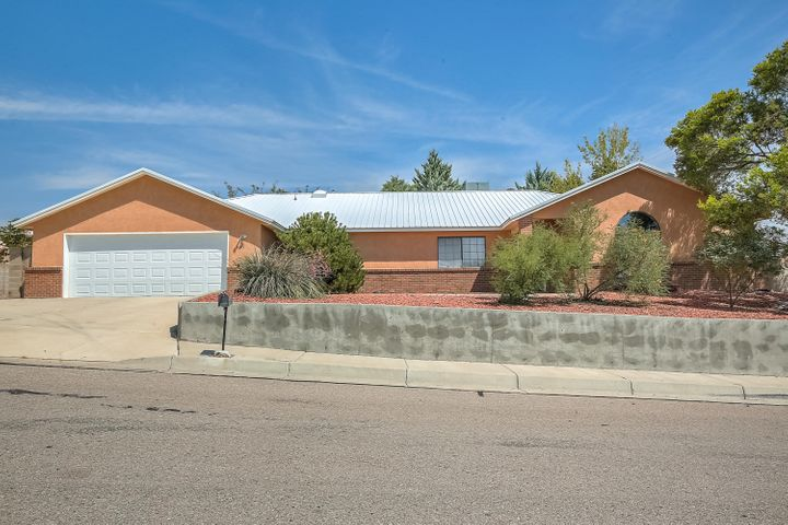 Rare treasure. Cheerful one story/open floor plan home drenched in natural light w/soaring vaulted ceilings/skylights... + a DREAM garage, side yard RV parking, & one heck of a centralized location! You'll love spending your life years here. Special features include comfortable refrigerated air, durable pitched / metal roof, tasteful engineered wood flooring in main areas, beautiful decorative built-in shelves (buyer may easily convert TV space back to a fireplace), master bathroom with separate shower from jetted tub and dual sinks / vanity, and best of all some dynamite outdoor living spaces either under the covered outdoor patio or in the fully-developed-and-matured, stunning, yet low-maintenance backyard gardens. The garage is at least 4-car tandem, a MUST-see for hobbyists!