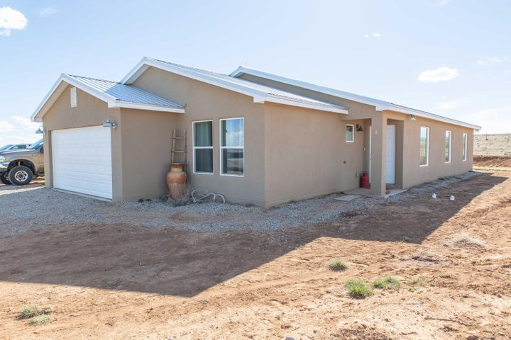 Built in 2017, this home sits on nearly 14 acres with natural gas and a private well.    This 4 bedroom 2 bathroom home boasts natural light, gorgeous views of the Pecos,Sandias and South Mountain. Spacious open floor plan , granite tops, subway tile back splash, SS appliances,  farm house sink, wood grain tile flooring, custom shelving, new carpet, metal roof, the list goes on and on. Minutes from shopping, schools and I40 access.  This home is a must see!