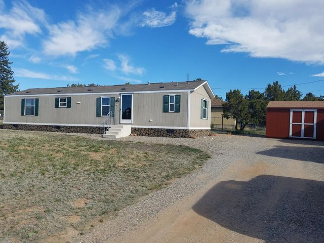 You don't see this type of quality very often on the market at a giveaway price in Mountainair, NM. This beautiful 2010 all electric home is nestled on a corner double lot. This home looks like new and boasts 2 large bedrooms and 2 full baths. It is a cozy home with thermal pane windows, thermal III insulation, and central heat and air. All kitchen appliances are included with the sale of the property. It is move in ready. The outside offers additional living space with a covered back deck and the exterior is skirted with custom rock skirting giving it a very pleasant appearance. The large property has a 10' X 16' Sturdy Built Shed for all your storage needs. This home is a great value in a great location and at a great price!