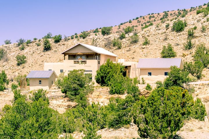This beautiful, tranquil Northern New Mexico style home is located on 1.9 acres in the Village of Placitas. Open concept w/ great flow and amazing views of the Sandia Mountains and western mesas! Custom touches throughout - lighted nichos and built-ins w/ seed-glass doors, beamed pine tongue-and-groove ceilings, custom plaster walls, stacked stone fireplace w/ Artisan gas insert, chef's kitchen featuring granite counters, deep sinks, custom tile backsplash, s/s appliances, gas cooktop, double ovens and lots of storage in knotty hickory cabinetry w/ under cabinet lighting. Master-on-main with spacious en-suite bathroom; 2 bedrooms upstairs w/ Jack & Jill bath and view balcony. Separate finished/heated studio would be a wonderful home office or artist's retreat! This home won't disappoint!