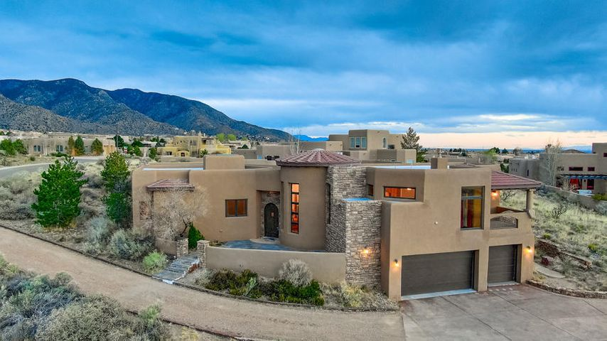 Distinctive West Highlands at  High Desert! Elegant Custom on approx .75 Acre Offering Views of the Sandias, City Lights, Sunsets & Open Space; Nearby Open Space Area! Private, enclosed covered & open patio & pool area w/views, perfect for family living & entertaining! Grand entry w/Rotunda type ceiling, dramatic greatroom opens to an upscale kitchen & dining room; Views from every room, deck & patios; sunny south facing patio w/ pool. Grand entry w/soaring ceilings & inviting custom paint & decor. Gourmet style kitchen w/custom cabinets , granite counters & stainless appliances. Great open living area & formal dining area on upper level. 4 BDRMS & study, 2.5 baths, sep master retreat w/luxury bath. 3 car garage. Ideal for family living & entertaining!  Elegance Abounds! Call now to view.