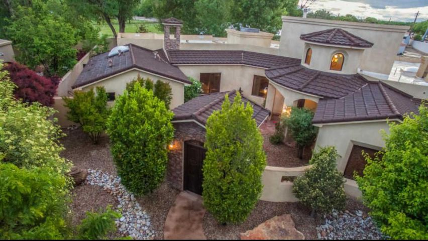 What a rare find! Built in 2008, this newer Tuscan style one-story home in gated North Valley subdivision has 4 bedrooms plus office/exercise room. Enjoy entertaining and relaxing in this gorgeous backyard with natural shaped, in-ground gunite pool and hot tub plus a long portal and  extensive ramada with fireplace. Kitchen features Viking, SubZero, and rustic exposed brick wall. Great room has 17 ft beam ceilings,  wood floors, stone fireplace and opens to the chef's kitchen. Spacious master suite has seating area, fireplace, luxury bath, huge walk-in closet, and easy access to hot tub. Conveniently located one block from  bosque walking trails, paved bike paths, and Bachechi Open Space Center & Park. Oversized 3-car garage. Space for outdoor RV parking on North side of garage.