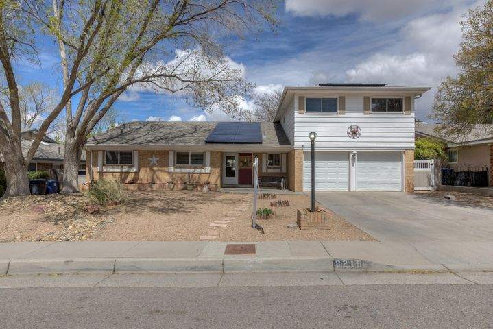 So much to offer on this large family home in the NE heights! New roof in 2017 and owned solar panel system by Evelar. Great quality laminate flooring throughout the house.  LARGE family room for the whole family to spread out in front of the wood burning fireplace.  Master bathroom remodeled in 2015 with double vanity, walk in tile shower and wonderful California Closet. Ceiling fans and 2 in blinds throughout. 3 bedrooms on main level and 2 more plus a hobby room with closet upstairs. Full bath upstairs for 2nd story dwellers.  Perfect for teens. Refrigerated air and updated windows. Extra 1/2 bath down stairs for company.  Backyard has stylish fencing and raised garden beds.  Large shade tree and covered patio. Great location and schools. CURB APPEAL!!