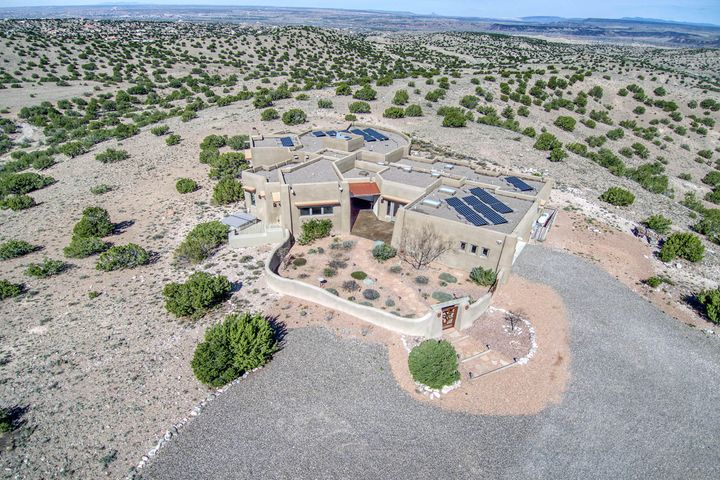 Spectacular in Placitas. This ''Green'' custom home offers a respite from the hustle & bustle of urban living. Inspired by Santa Fe's pueblo style, the home is set on 10 acres and boasts Travertine floors, custom mosaics, clay walls, a chef's kitchen and windows that show off the dramatic 360 mountain/desert views like picture frames and a live-in guest wing with separate entry. The Gold Level Green Home certification for this Placitas home was achieved by careful design and artisan craftsmanship. Built with double stud & Rastra walls, insulated concrete, to keep cool in afternoon heat & warm on cold nights. Electricity for all modern living conveniences along with heating, cooling and hot water is generated 365 days/year through 44 photo voltaic panels & 279 days of Placitas sunshine.