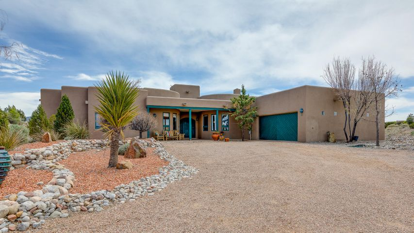 Gorgeous Southwest Contemporary custom home on one of the best View lots. Chef's Kitchen with Stainless appliances including cooktop, wall oven, microwave, prep sink. Gorgeous granite counters, Cherry cabinets, large pantry & built in breakfast nook. Formal dining w/cozy kiva FP. Master Suite with 2 way  fireplace, glass block shower & soaking tub + large walk-in closet with built-ins. Guest bath with custom sink, vanity & walk in shower. Sunrises/Sunsets with Views of Sandia Mtns /Mesas. Sparkling Pool, auto cover, fabulous outdoor space, beautifully landscaped. Refrigerated air, radiant & forced air heating. Oversized 2 car garage.