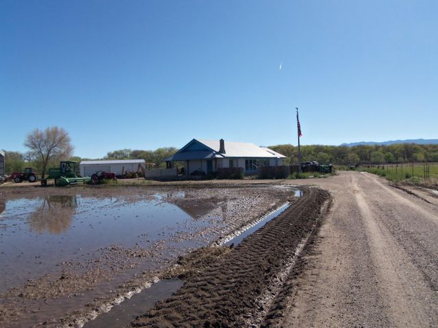 Custom Adobe home on irrigated 4.14 acres. Home has raised ceilings with large beams, country kitchen. One bedroom is in the loft area adjoining an office or hobby room.  Master bedroom has Kiva fireplace.  Home sets back off highway with view.  Property includes large metal buildings. One is a 40X60 with 6 inch concete floor with prower, one is a 22X40 with concrete floor with power  and has a 22X60 open hay barn.  This is a must for that farmer who wants equipment storage and hay barn.