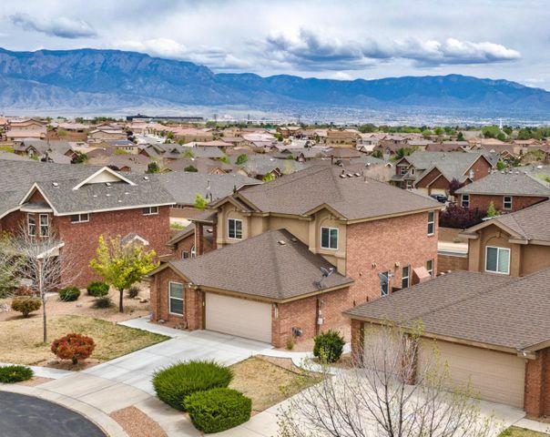 Enter the gated community of Cabezon to this exquisite 5 bedroom/3 full bathroom Pulte brick home located on a cul de sac with master suite balcony views of the Sandia Mountains.  Upon entry high ceilings, natural light, and a gleaming wood staircase greet you.  The wood floors exude warmth and flow throughout the two living areas and formal dining room on the main floor. Bright and functional kitchen boasts granite countertops, GE Profile stainless appliances w/ built in electric stove and opens conveniently into the second living area with gas fireplace. 2 bedrooms and a full bathroom are located on the main floor-the second bedroom w/ its double entry doors is spacious and can easily serve as a game room, office, or in-law suite!