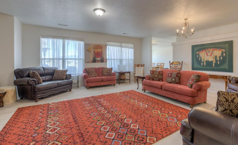 Elbow room... inside & out! This thoughtfully built home offers a truly open & spacious floorplan and elegant architectural design featuring beautiful  elevation, tiled roof, rotunda foyer with raised ceiling & clerestory windows, natural light pours in softly throughout, 2+ living areas, functional kitchen open to a cozy family room or dining room with fireplace, separate and expansive owner's retreat with huge picture windows framing the Sandias and an expansive sitting area, luxurious bathroom with double sinks, separate shower/tub, & walkin closet.  front living area works as an office, play room or a formal living or dining room. If you can dream it, there is room for it on this 1+ acre lot w/ an east facing backyard, just 5 minutes to city conveniences! It could be your Dream Home!