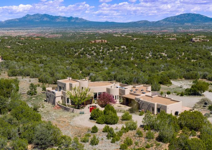Custom pueblo style home radiates southwest elegance and charm. Situated on just over 11 acres in the premier San Pedro Creek Estates subdivision this home was carefully designed to take in the 360-degree breathtaking views of the Sandia, Ortiz, and Sangre De Cristo Mountain ranges. Welcoming courtyard guides you into the front entry, where one is immediately drawn into the spacious great room w/ its curved wall of windows showcasing picturesque views. Just shy of 4,000 sqft, this property offers so much space and storage w/ 4 bedrooms, 4 bathrooms, huge office/rec room w/ wet bar & multiple outdoor patios (both covered & uncovered) to enjoy the beautiful outdoors. Gourmet Chef's kitchen allows for ease of entertaining w/ its open layout & features high-end SS appliances (Dacor, Sub Zero)