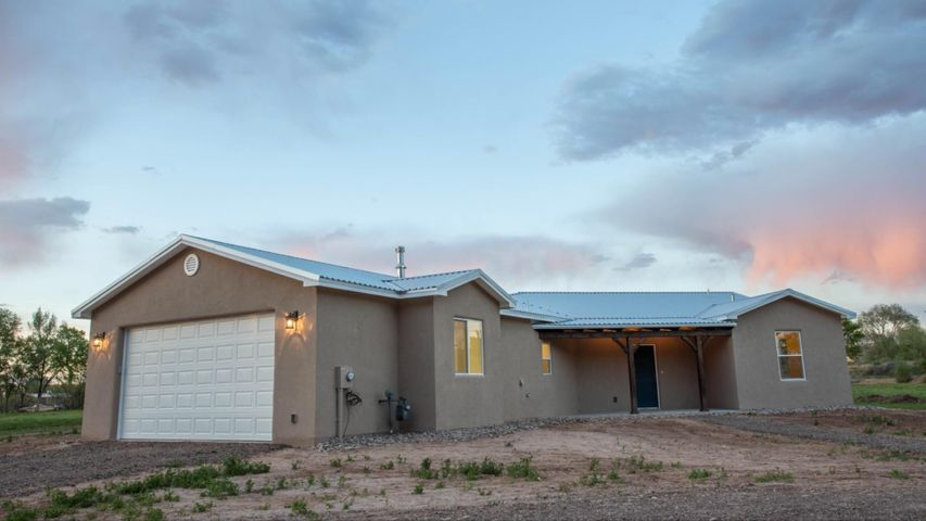 BRAND NEW!!! Prior Parade of homes winner built this quality Custom 3 Bedroom two-Bathroom home on almost 2 acres of irrigated land planted with Alfalfa. Home has 3 patios to enjoy the colorful sky, each boasts routered and sanded beam work. Patio lid is rough sawn beetle kill logs from the Manzano  Mountains. Kitchen is stunning with fantastic great room. Shaker panel interior doors match the custom cabinets with solid surface counter tops and soft close drawers. Kitchen island has large farm sink with Live Edge. Custom reclaimed barn wood accents located in living area and master bedroom recovered locally.  Large soaker tub in the master. Huge pass through shower and walk in closet. Vaulted ceilings and beautiful lighting fixtures. Home is located close to both Los Lunas and Belen.