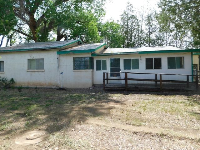 Adobe home on 1.3 acres with mature trees and MRGCD irrigation availability.  This 3 bedroom 1 bath home sits at the end of a dead end road.  Lots of potential here!  Property is being sold in as-is condition.  seller will not make any repairs.