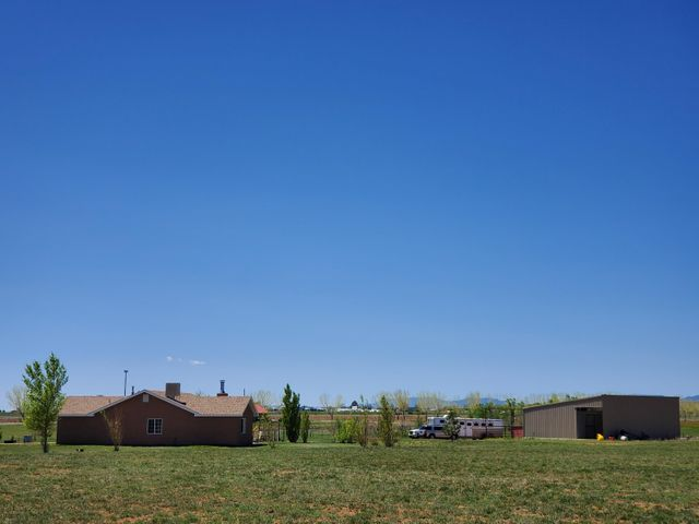 Beautiful Property! Horses, Grass, Pasture. 4  Bedroom/2 Bathroom, open floor plan. sky lights, sunny, tile /carpet, large living room with gas fireplace.  Insulated/Sheet-rocked, 2 car garage.  Metal Barn with 3 horse stall/run with spacious tack room.  Fenced pasture.  Beautiful and serene!