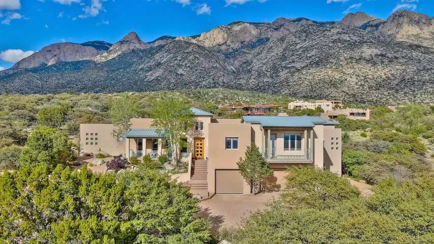 Stylish, sophisticated, private home nestled into the magnificent Sandia mountains in Sandia Heights North. Designed by renowned architects, this home is perfect for watching magnificent sunsets and enjoying the city lights. Set amongst boulders with a stunning sculpture garden and pond, the Zen like quality is evident. Each of the 3 bedrooms are set apart for privacy each with private bath. Incredible living areas surround, with remarkable kitchen and great room centering the home. Imagine the views while entertaining, relaxing, or working from a home office area overlooking the mountains.