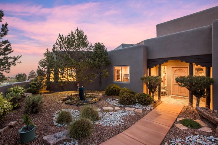 Dynamic views of the Sandia Mountains, the City Lights, and the beautiful high desert await a lucky buyer from this beautifully constructed custom Pueblo style home. Kitchen features rich granite, furniture grade custom cabinetry, high end appliances, and a huge island with tons of counter space. The family room features a 2 story ceiling with rich wood ceiling details, a custom Kiva fireplace, and windows to take in the views in every direction. The master suite, located upstairs to take advantage to the dramatic views offers a luxurious bath, dual walk in closets, a sitting area with fireplace, and a wrap around deck. All other bedrooms offer en-suite baths. A home theater, beautiful outdoor living space w/ outdoor kitchen, and an oversized 4 car garage wrap up this great home.