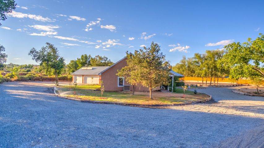 VIEWS!! In Corrales.  This is country charmer has a wrap around porch for those early morning risers.  Many updates, ask for feature list. The 4 bedroom home with 3 full bathrooms is an open concept construction for living space.  There is an additional office area off the garage and Northern yard area with separate access. Light and bright.  Cathedral ceilings.  NEW Septic System, 2 Wells (one for irrigation and one for the home).  NEW Gas Range Cooktop with griddle, NEW 2 ovens, NEW Microwave.   2 fireplaces.  1 fireplace has an electric igniter with switch to control on/off feature.  This is on over 1.7 acres and would be a beautiful horse property.  Room to add casita or barn.  Owner will consider paint color change of the buyer's choice with accepted offer.